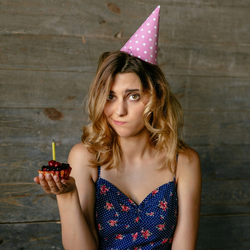 woman holding a cupcake on her birthday